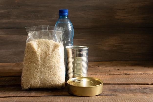 暗い木製の背景に缶詰食品とシリアルのパケット。食品ストックの概念 Premium写真