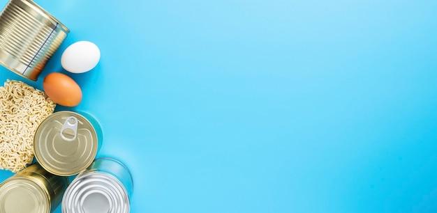 Консервы, яйца, макаронные изделия, изолированные на синем фоне, copyscape.