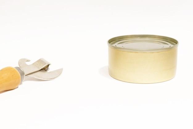 Консервы для домашних животных на белом фоне и консервный нож. вид сбоку