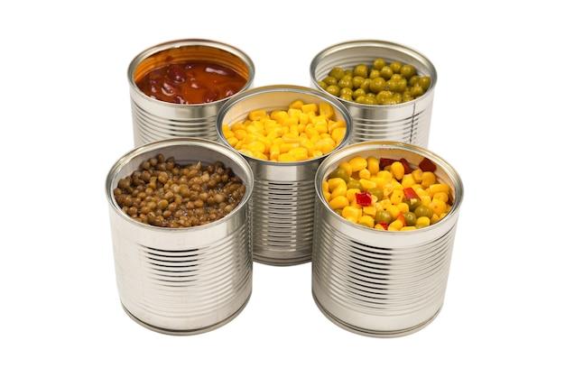 白い背景の上の缶詰食品。グリーンピース、豆、トウモロコシ、レンズ豆。