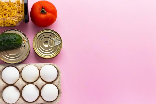 Консервы, свежие овощи, помидоры и огурцы, яйца чичен и макароны в стеклянной банке на розовом фоне