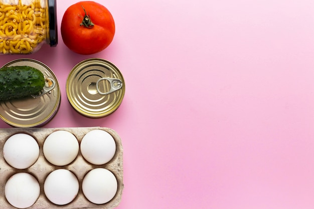 Canned goods, fresh vegetables, tomato and cucumber, chichen eggs and pasta in glass jar on pink background