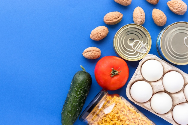 Canned goods, walnuts, fresh vegetables, tomato and cucumber, chichen eggs and pasta in glass jar on blue background