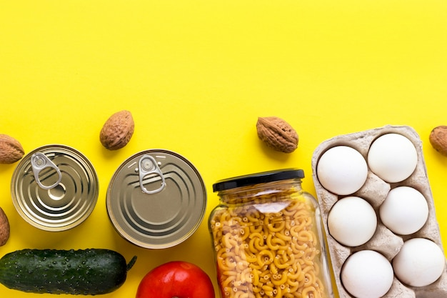 Canned goods, walnuts, fresh vegetables, tomato and cucumber, chichen eggs and pasta in glass jar on pink background