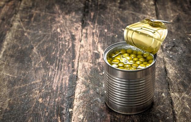 木製の背景に缶詰のグリーンピースの缶詰