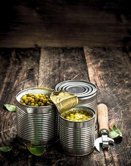 木製の背景にオープナーと缶詰のグリーンピースの缶詰