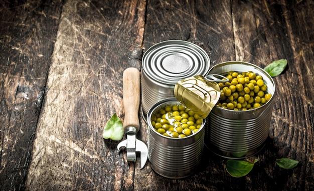 オープナー付きの缶詰のグリーンピースの缶詰。木製の背景に。