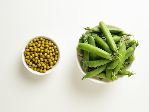 白いボウルの缶詰のグリーンピースと白いボウルのグリーンピースのポッドは、白いテーブル、上面図の隣に立っています