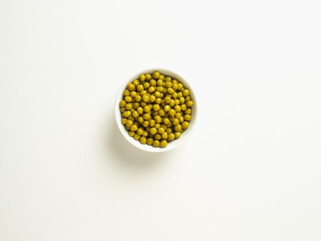 白いテーブルの上の白いボウルに缶詰のグリーンピース、、上面図