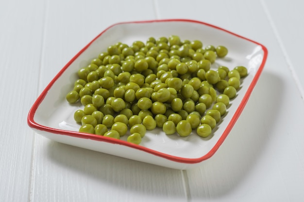 Canned green peas in a white plate with a red border. dietary vegetarian food.