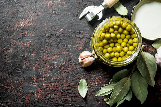 Canned green peas with bay leaf and garlic cloves on rustic table