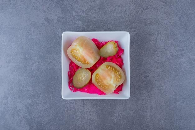 회색 위에 흰색 그릇에 통조림된 녹색 토마토입니다.