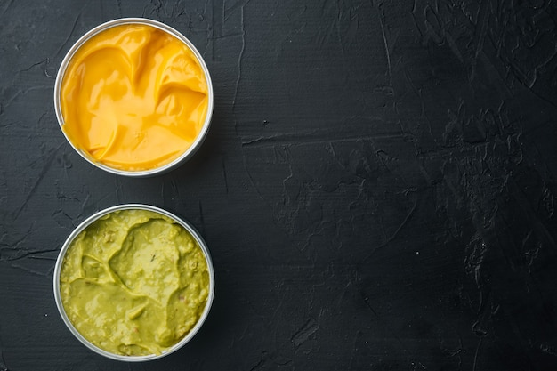 Canned guacamole and cheese dip in can, on black table, top view or flat lay