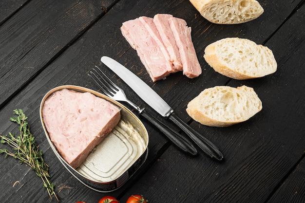 缶詰のハムスライスサンドイッチセット、黒い木製のテーブルの背景に