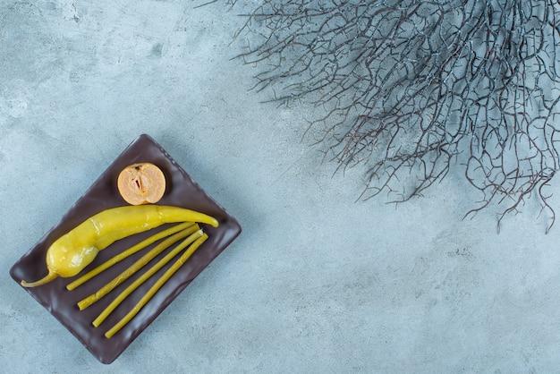 통조림된 고추에 사과, 접시, 대리석 테이블에 막대기.