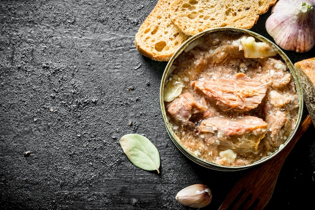 Canned meat with garlic, bay leaf and slices of bread on rustic table