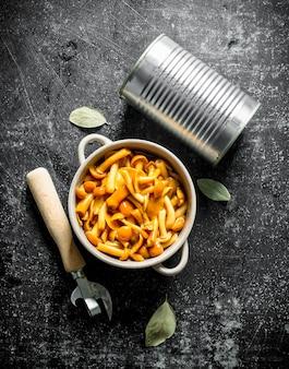 ブリキ缶と暗い木製のテーブルの缶切りが付いているボウルの缶詰のきのこ