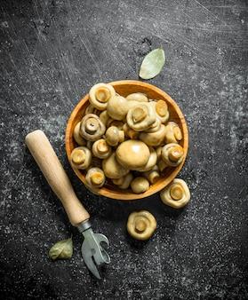 Консервы из грибов на деревянной тарелке с открывашкой. на темной деревенской поверхности