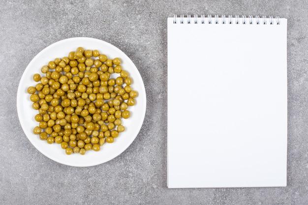 ノートブックと白いプレート上の缶詰のエンドウ豆