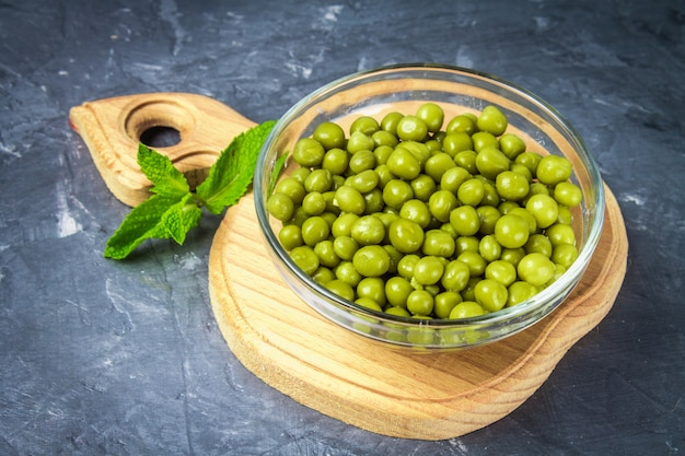 Canned peas in a wooden plate on a gray concrete background.