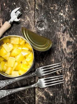 Canned pineapple in a tin can with forks and opener.
