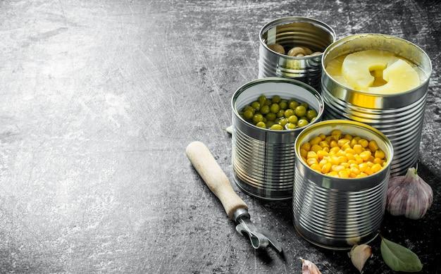 素朴なテーブルの上の開いた缶の缶詰のパイナップル、グリーンピース、トウモロコシおよびきのこ。