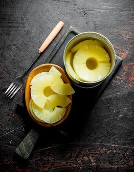 缶詰のパイナップルとブリキ缶と皿。暗い素朴な背景に