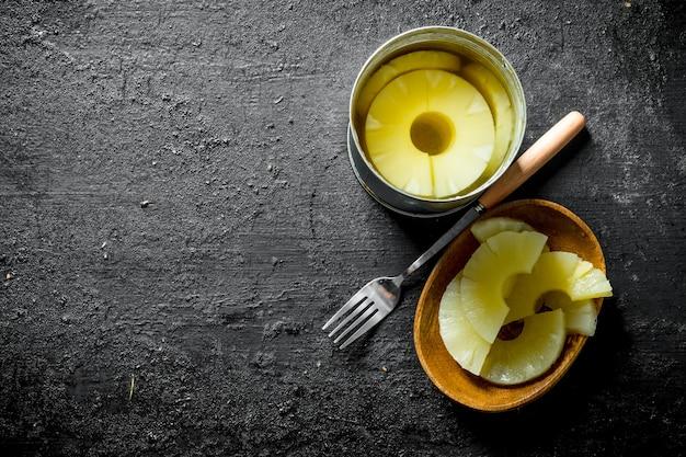 フォークで皿にパイナップルの缶詰。黒の素朴な背景に