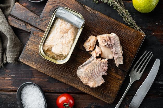 Консервы из лосося, рыбные консервы, на деревянной разделочной доске, на старом темном деревянном столе