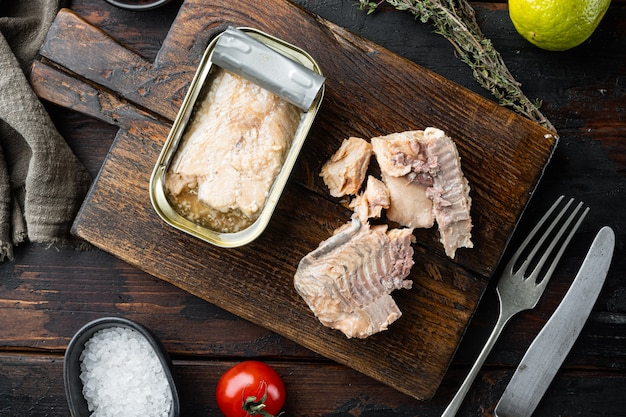 Canned salmon, fish preserves, on wooden cutting board, on old dark wooden table