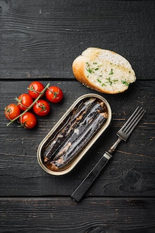 Canned seafood preserved in oil set, on black wooden table background, top view flat lay, with copy space for text