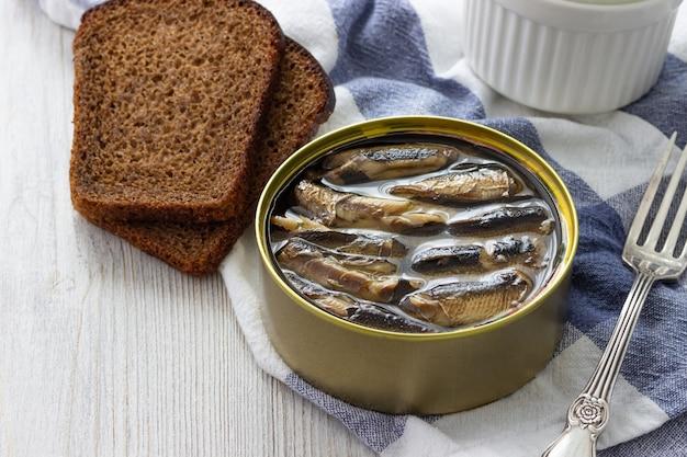 Консервы шпроты в жестяной банке с хлебом для бутерброда