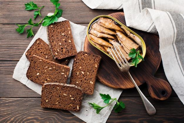 Консервированные шпроты в жестяной банке с вилкой с хлебом для приготовления бутерброда на темно-коричневом фоне. выборочный фокус. деревенский стиль. вид сверху. скопируйте пространство.