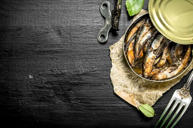 Canned sprats in a tin can. on the black chalkboard.