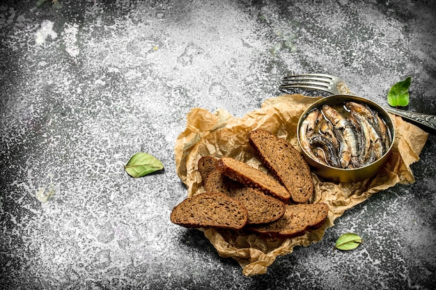 Canned sprats in tin can with rye bread. on a rustic background.