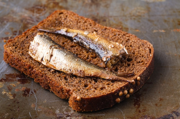 Canned sprats in tin can with rye bread