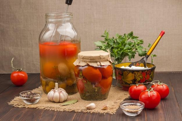 통조림 토마토, 마늘 및 향신료. 수제 발효 제품. 건강한 겨울 영양. 검은 나무 표면.