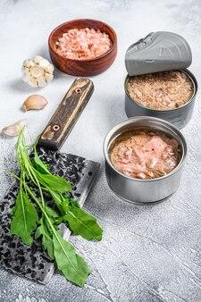 缶詰のマグロ缶、丸ごと、みじん切り。灰色の木製の背景。上面図。