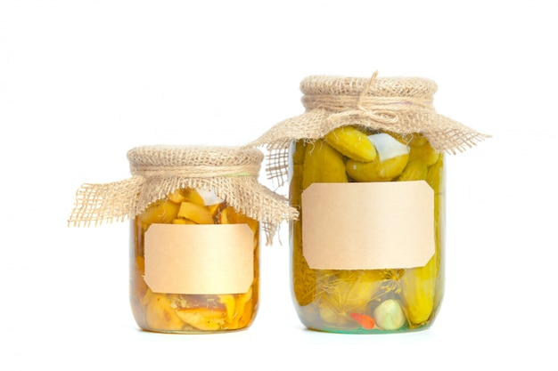 Canned vegetables in glass jars isolated on white