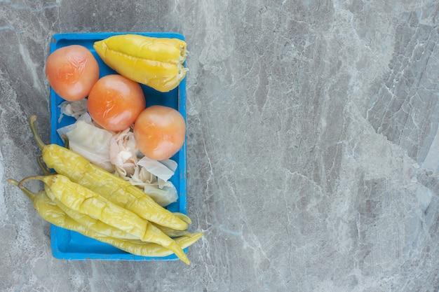 Консервированные овощи на синей деревянной тарелке. домашний рассол.