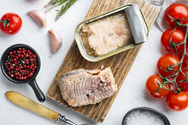 缶詰のワイルドピンクサーモンセット、木製のまな板、ハーブと材料の白いテーブル、上面図フラットレイ