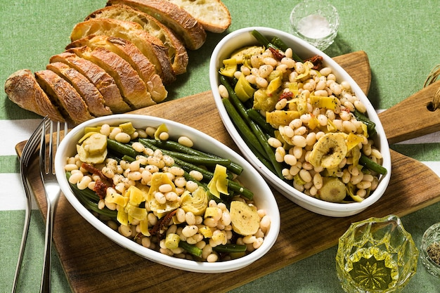 Cannellini nutritious white bean salad with green beans, sun-dried tomatoes and artichokes in oil.
