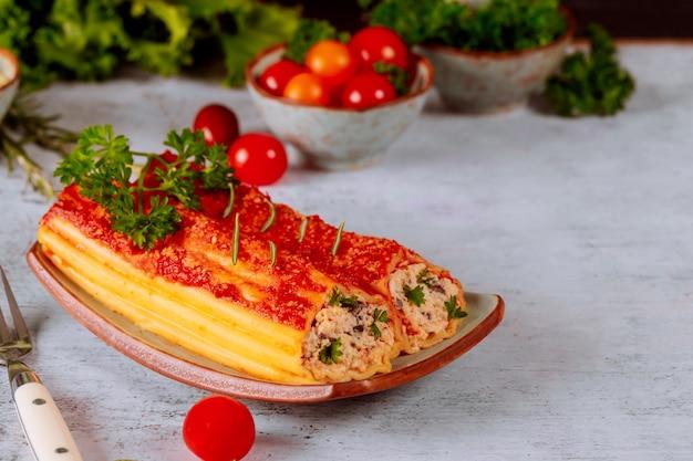 Макароны каннеллони джамбо на тарелке с помидорами