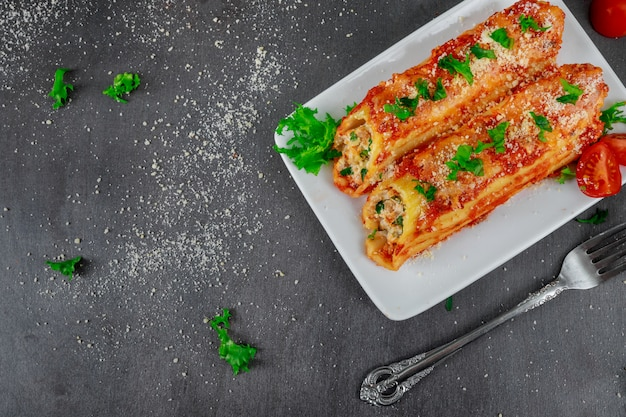Cannelloni on a plate with meat and tomato sauce