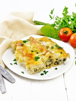 カッテージチーズとほうれん草のベシャメルソースをプレートに詰めたカネロニ、ナプキン、トマト、パセリを明るい木の板の背景に