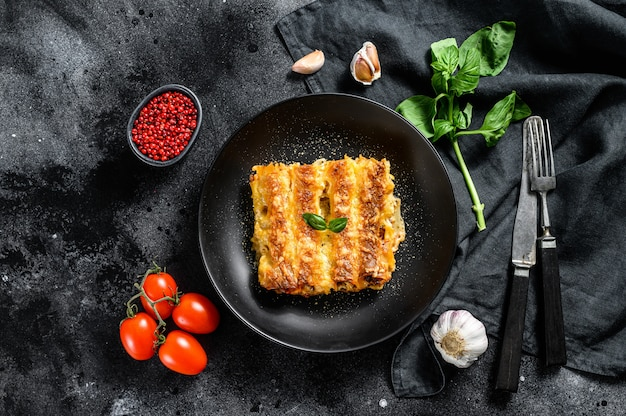 Каннеллони с говядиной и томатным соусом. итальянская домашняя паста. черный фон. вид сверху