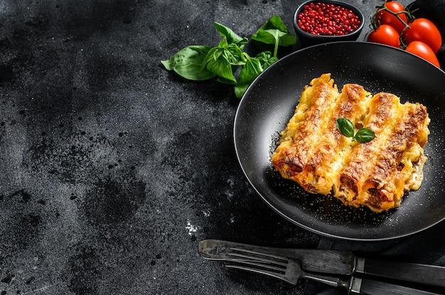 Каннеллони с говядиной и томатным соусом. итальянская домашняя паста. вид сверху. копировать пространство
