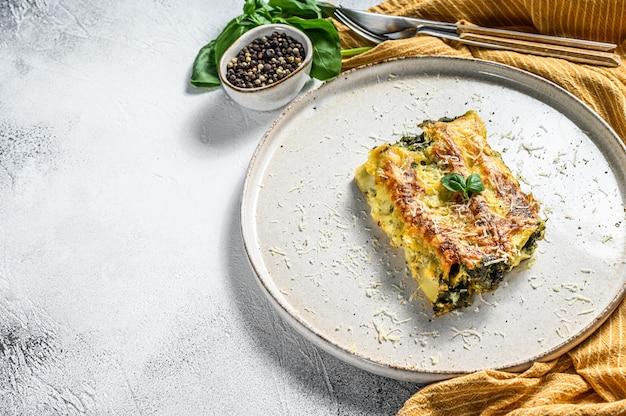 Каннеллони с рикоттой и шпинатом. итальянская кухня. серый фон вид сверху. копировать пространство
