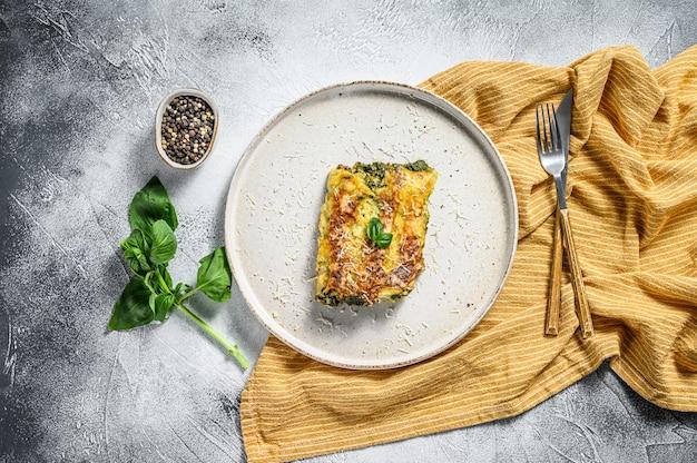 Каннеллони с рикоттой и шпинатом. итальянская кухня. серый фон вид сверху