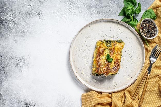 Каннеллони с рикоттой и шпинатом. итальянская кухня. серый фон